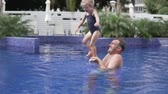 Dad plays with his little daughter in the outdoor pool. They splash in water and laugh. The man holds the girl by the legs and lifts her up, above the water level, the child seeks balance. Weekend wit