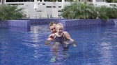 Dad swims in the pool with his little daughter. A man raises the baby in his arms above the water and the child holds the balance. Dad teaches baby to swim. Educational games in the pool with parents Стоковые видеозаписи