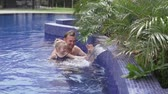 Dad with a little daughter swim in the pool. A man and his daughter look at the fountain in the pool and touch the water. Dad teaches a child to swim. Relax at the hotel by the p Стоковые видеозаписи