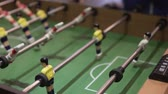 football field : People play table football. They pull the handles and the players are spinning. Close-up of the game table and players Stock Footage