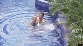 pływak : Dad does gymnastics to his little daughter in the pool. A man teaches swimming a little girl in an outdoor pool. Baby swimming with parents