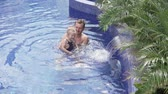Dad plays with his daughter in the pool. A man does water gymnastics to a little daughter. He turns the child right and left