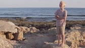pihy : Boy blond walks on the beach. The child stands near the sea on the beach in the sand Dostupné videozáznamy
