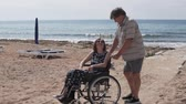dede : An elderly man carries a woman in a wheelchair along the sea. The husband carries his wife with a broken leg in the wheelchair past the window. A woman with a broken leg in an orthosis in a wheelchair