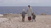 ハグ : Mom with children goes to the sea. A woman holds the hands of her children and walks along the rocky shore to the sea. The family looks at the beautiful sea from the cliff.