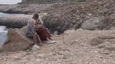 ハグ : Mom gently strokes the children on a halt by the sea. The family sits on a rock by the sea and talks. Beautiful, cute video from a spring vacation in Cyprus