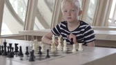 lad : Handsome blond boy playing chess. The boy is waiting for the opponents move. Stock Footage