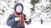 vállkendő : The boy ties a scarf around his neck for a winter walk through a snowy forest Stock mozgókép