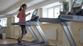 尻 : Young sexy woman running on a simulator treadmill in the hall. She sets up an exercise program on screen.