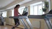 尻 : Woman runs on the simulator treadmill in a sports club. The girl is engaged in sports on the simulator from the gym
