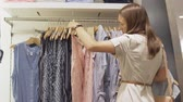 szafy : Woman chooses a dress in the store. Stylish customer buys a dress in the store