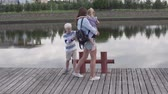 moederdag : Mother and children walk along the embankment of the river in summer. Family at the evening promenade. Mom talks with her son and holds her daughter in her arms Stockvideo