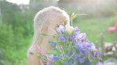 borboletas : Beautiful little girl with a bouquet of blue bells stands in the garden. Baby smells blue flowers at sunset Stock Footage