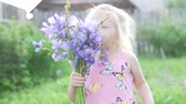 borboletas : cute little girl sniffing a bouquet of blue irises. A child with a bouquet of wild flowers is standing in a field at sunset and smiling, gentle baby, close-up