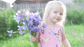 borboletas : little girl blonde sniffs a bouquet of blue irises. A child with a bouquet of wild flowers is standing in a field at sunset and smiling. Tender fashionable baby with flowers on the farm