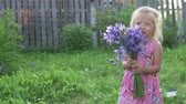 borboletas : Beautiful little girl holding a bouquet of blue flowers and laughing. Shaggy baby on the farm with a bouquet of irises smiling at sunset. Beautiful summer video from the cottage
