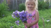 borboletas : The little girl laughs with a bouquet of flowers in her hands. Summer farm Stock Footage