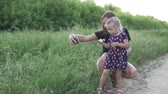 moederdag : Beautiful young mother makes selfie with her daughter on the phone. A woman is photographed with her daughter in the field and watch pictures laughing