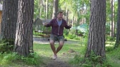 basis : A man rides a swing in a natural park. A man relaxes on a swing at the camp site in summer