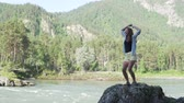 mundo agua : Beautiful woman jumping for joy and raises her hands up. Victory, rast overcoming the route. A tourist raises her hands up and jumps on a stone by a mountain river. Slow shooting Archivo de Video