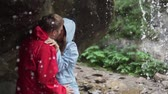 ハグ : A man and a woman are standing under a waterfall and kissing. Dad lovers in jackets stand under the water of the waterfall and kiss passionately. Slow shooting, Altai. St. Valentines Day 動画素材