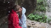 ハグ : Family day. Lovers kiss under a waterfall. A couple on a hike stands under a stream of a waterfall in non-wet jackets, they gently kiss and laugh