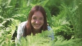 helecho : A woman sits in the fern thickets and laughs. Wildlife, summer, Altai, close-up