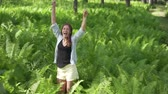 acconciatura : A happy woman jumps and raises her hands up in the fern bushes. Slow shooting. Happy tourist dancing on the background of Altai wildlife