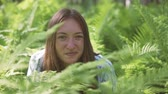 helecho : A woman sits in the fern thickets and smiles. Wildlife, summer, Altai, close-up Archivo de Video