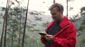 sarma : A man in a forest near a mountain river is looking at a mobile phone. Wildlife, mountain under the Altai, Russia. Rainy morning hiking without internet