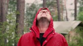sarma : A man in a hood in a red jacket standing in the rain in the forest. Close-up face, slow motion Stok Video