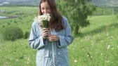 toplamak : Woman in a raincoat walks on a field with flowers. She collects a bouquet of daisies and smells wildflowers.