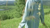 elbise : A woman walks on a green field with flowers. Back shot