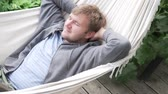 perezoso : Relaxed man lying in a hammock in the summer on the veranda.
