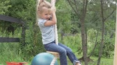 brinquedos : Little girl riding on a wooden swing in the summer. Vídeos
