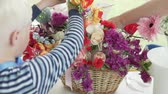 werkstatt : The boy collects a bouquet of artificial flowers. Master class floristry for children