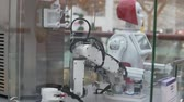 robô : A robot makes ice cream in a mall. The robot takes a bowl and pours ice cream into it.