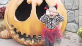 Little funny girl celebrates halloween. A baby in a suit stands by a giant pumpkin and laughs Wideo