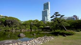kansai : circle around of tall and famous building setting behind of a japanse landscaping garden in osaka.