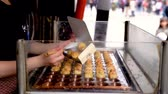 doboz : Osaka, Japan-April 14, 2018: chef using chopsticks to put takoyaki into the outer box from the stove