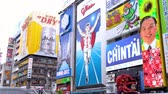 bordo : Osaka, Japan-April 14, 2018: famous Glico runner sign is the biggest billboard on the advertising wall, beside is a huge red octopus