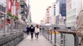 dotonbori : Osaka, Japan-April 14, 2018: Japanese young couple dating and relaxing walking along the river Stock Footage