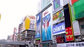 ahtapot : Osaka, Japan-April 14, 2018: people walking on the Ebisu bridge with many advertisements hanging on surrounding buildings Stok Video