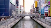 dotonbori : Osaka, Japan-April 14, 2018: clean river with a bridge above it, the bridge is full of people walking on it Stock Footage