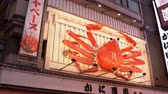 коммерческий : Osaka, Japan-April 15, 2018: cute large crab sign of the restaurant is hanging on the wall and moving