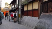 lehúzó : Kyoto, JAPAN - APRIL 18, 2018: many tourists walking on the street, car puller resting while passenger looking at the Japanese wooden building