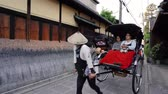 lehúzó : Kyoto, JAPAN - APRIL 18, 2018: Japanese traditional pulled rickshaw on the street with joyful passengers sitting on it