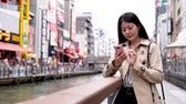 dotonbori : confident office lady standing next to the river sending text to her kids after work