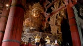 antiguidade : huge god statue made of gold sitting peacefully in the temple Stock Footage