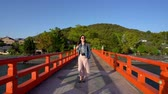 배낭 여행 : elegant lady flicks hair while walking through the red bridge 무비클립